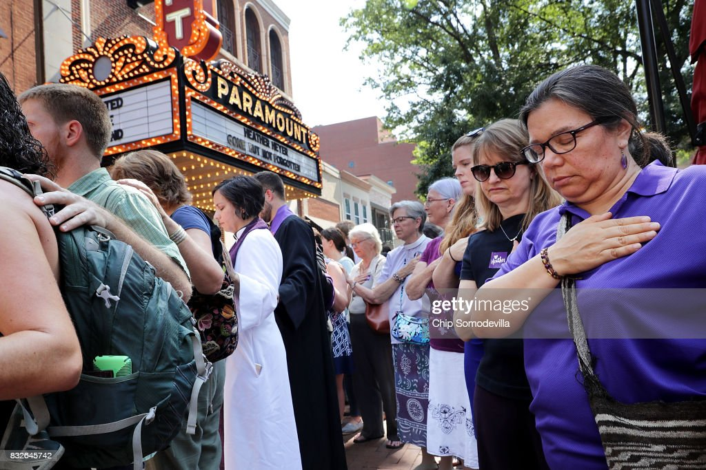 Clergy observe a moment of silence during the memorial service for Heather Heyer outside the Paramount Theater August 16, 2017 in Charlottesville, Virginia. The memorial service was held four days after Heyer was killed when a participant in a white nationalist, neo-Nazi rally allegedly drove his car into the crowd of people demonstrating against the 'alt-right' gathering.