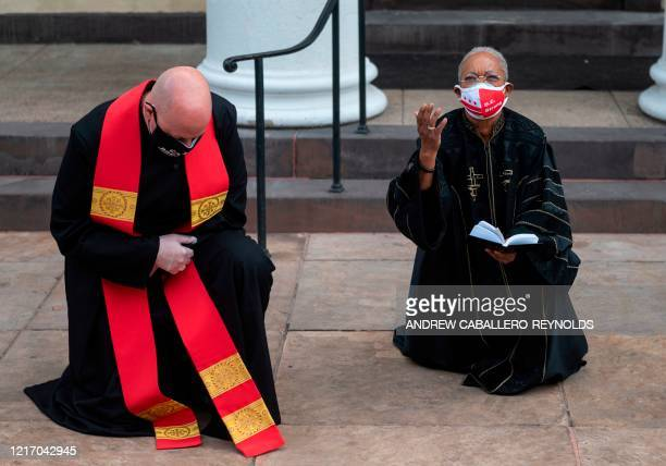 Clergy pray in front the St John's Episcopal Church across the street from Lafayette Square and near the White House in Washington DC on June 2 2020...