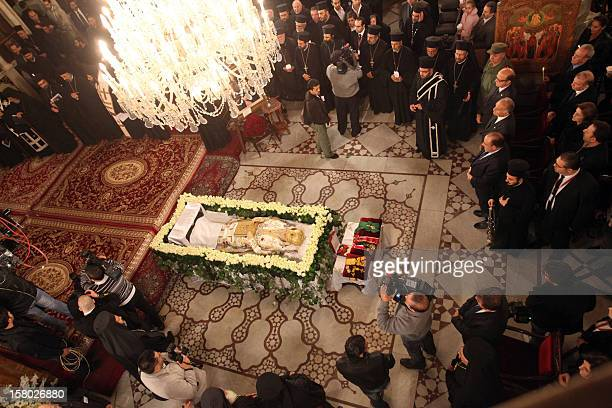 Clergy stand around the body of Greek Orthodox Patriarch of Syria Ignatius IV Hazim is layed out at the Mariamite Cathedral of Damascus on December 9...