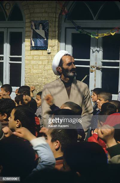 Clergyman headmaster of a boys primary school supervises the boys while they chant slogans during the break hour in south Tehran, 2nd February 1986.