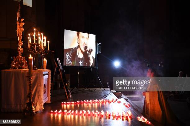 TOPSHOT A clergyman kneels during a prayer vigil in memory of late French rock star Johnny Hallyday at the SaintRoch Church in Paris on December 7...