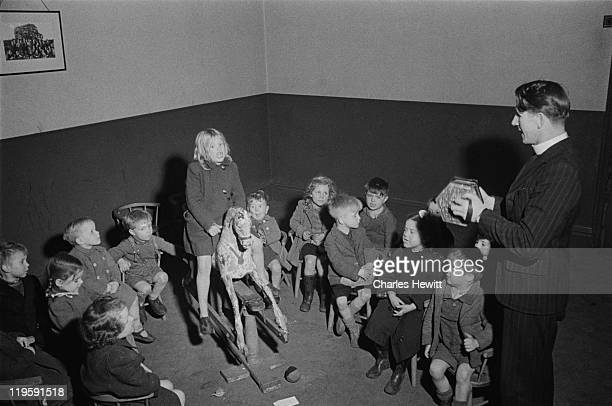 A clergyman plays the concertina for a group of children in a church on Christmas Street formerly Noel Street in the south London borough of...