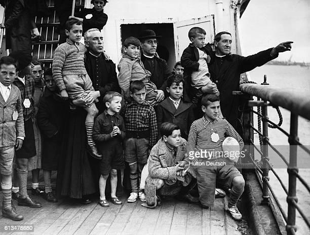 A clergyman points towards the English coast as the ocean liner Habana draws into dock carrying some 4200 Basque children who have been evacuated...