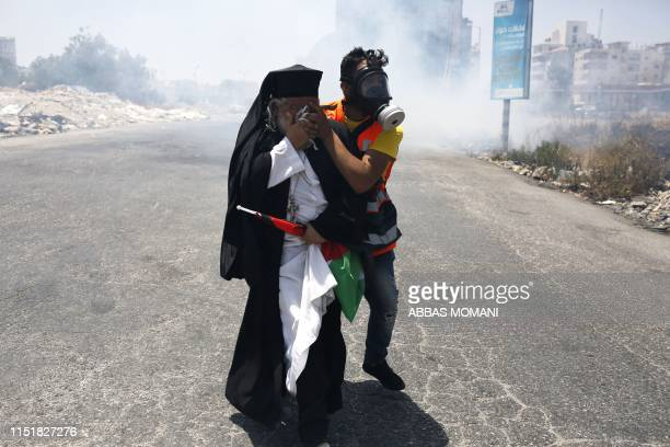 A clergyman reacts to tear gas fired by Israeli forces during a protest against a USsponsored Middle East economic conference in Bahrain on June 25...