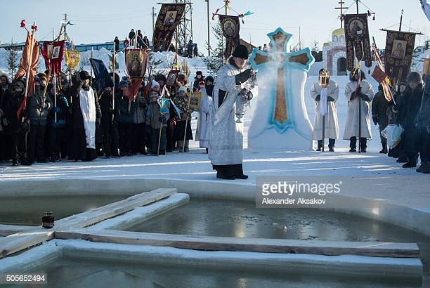 A clergyman sanctifies the waters of the Irtysh River on Epiphany on January 19 2016 in Tobolsk Siberia Russian Orthodox celebrate epiphany by...