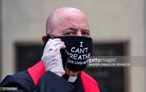 A clergyman speaks on his cell phone in front the St John's Episcopal Churcha cross the street from Lafayette Square and near the White House in...