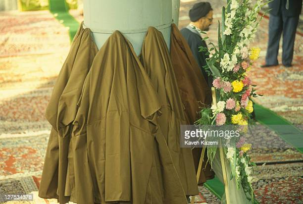 Clergymen hang their cloaks on a makeshift hanger while attending a memorial service for Ayatollah Khomeini, held at Friday Prayers at Tehran...