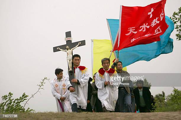 Clergymen lead Catholics to the simulated crucifixion site of Jesus at Cross Hill at Paowo Village on May 3 2007 in Meixian County of Shaanxi...