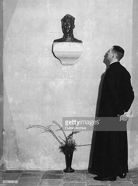 A cleric examines the bust by Eric Kennington of British soldier adventurer and author T E Lawrence known as Lawrence Of Arabia in St Paul's...
