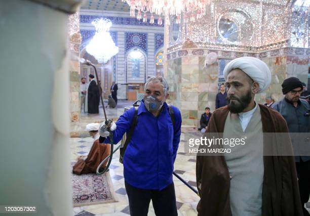 A cleric looks at an Iranian sanitary worker disinfecting Qom's Masumeh shrine on February 25 2020 to prevent the spread of the coronavirus which...