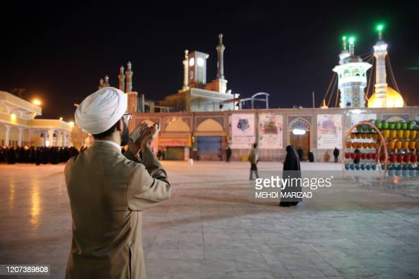 A cleric prays outside the Fatima Masumeh shrine in Iran's holy city of Qom on March 16 2020 Iran closed four key Shiite pilgrimage sites across the...