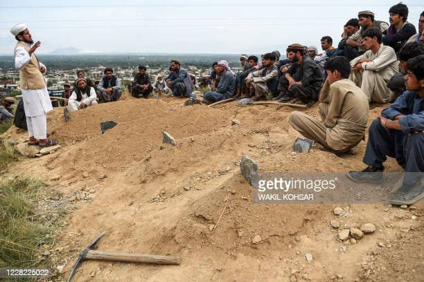 Cleric speaks as relatives of victims attend a burial ceremony after people died in the flash floods that affected the area at Sayrah-e-Hopiyan in...