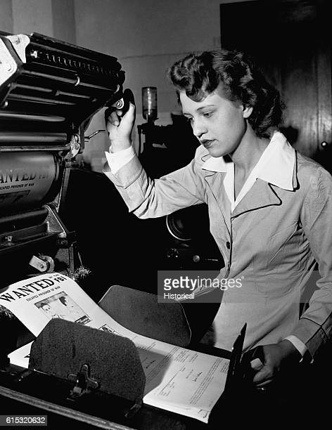 A FBI clerical worker makes identification orders on a printing press during World War II Ca 19411945