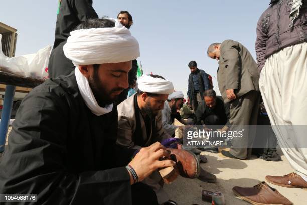 Clerics volunteer to polish the shoes of fellow pilgrims as thousands of Iranian Shiite Muslims prepare to cross the Mehran border point between Iran...