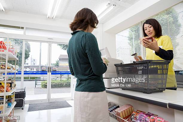 clerk and customer at convenience store - convenience store counter stock photos and pictures