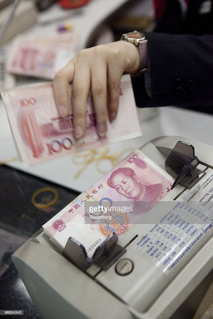 A clerk at a branch of the Bank of China Ltd  counts one hundred