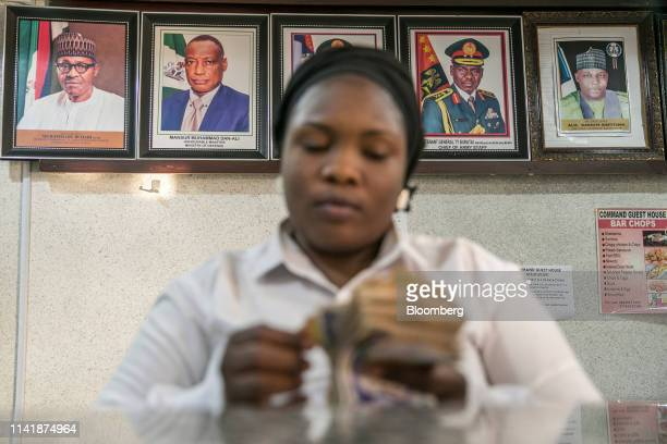 A clerk at a hotel reception counts Nigerian naira banknotes as portraits of the current president Muhammadu Buhari and other dignitaries are...