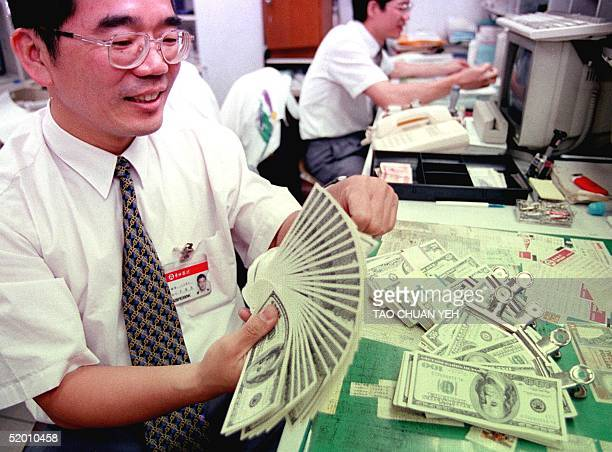 A clerk at a Taipei bank smiles while counting stackes of US dollar bills as the Taiwan dollar soared 17 percent to close at 34101 to the greenback...