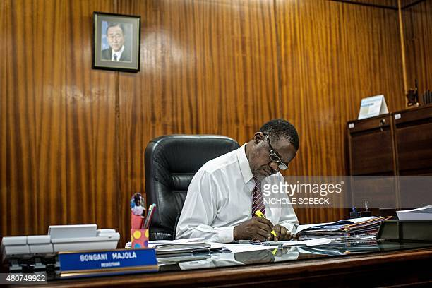 Clerk Bongani Majola works at his desk at the International Criminal Tribunal for Rwanda on December 3 2014 in Arusha Two decades of work and 61...