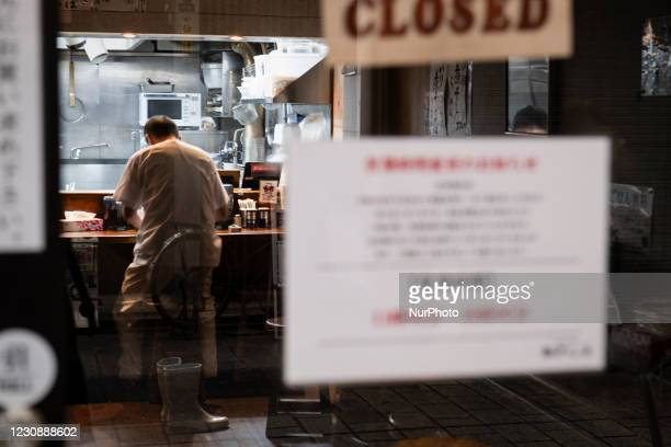Clerk cleans up at the closed Ramen shop with a sign of shorten business hours due to the state of emergency in Tokyo, Japan on 28 January, 2021.