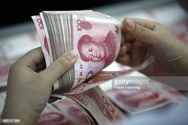 A clerk counts Renminbi banknotes in a bank outlet on August 26 2015 in Huaibei China China cut both the interest rate and the reserve rate on...