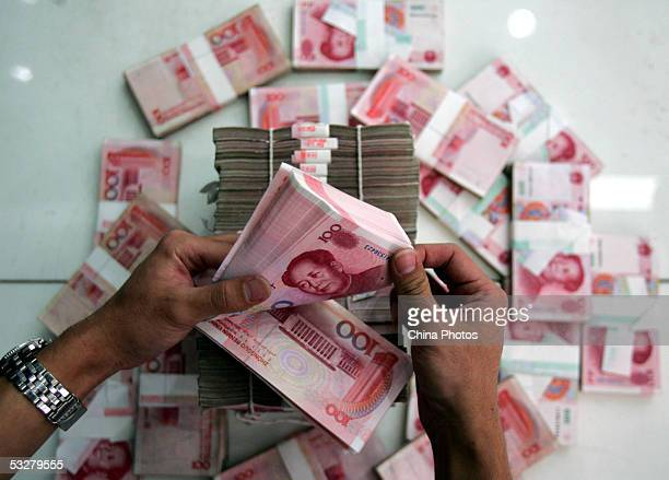 A clerk counts stacks of Chinese yuan at a bank on July 22 2005 in Beijing China The People's Bank of China the central bank announced on July 21 to...