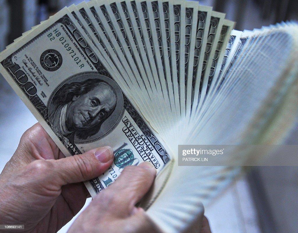 A clerk counts US dollar bills at a bank : News Photo