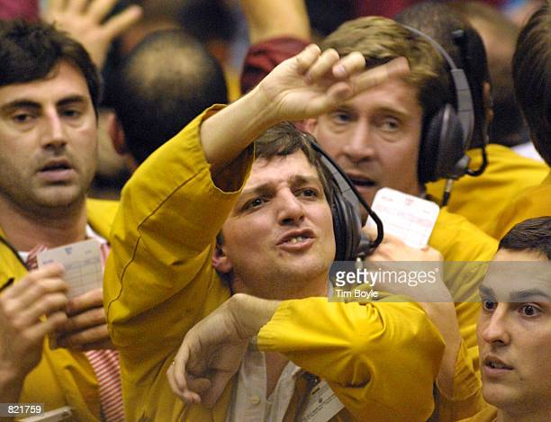 A clerk flashes handsignals as he works the Eurodollar Futures pit March 20 2001 at the Chicago Mercantile Exchange after the Federal Reserve...