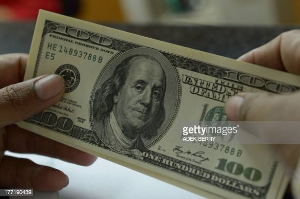 A clerk holds US 100dollar notes at a money changer shop in Jakarta on August 22 2013 The Indonesian currency the rupiah on August 20 hit a fouryear...