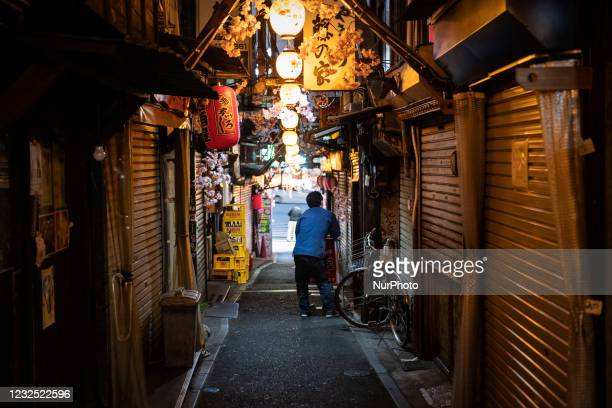 Clerk of a Japanese bar prepare for closing beside a deserted alley in Tokyo, Japan on April 25, 2021.