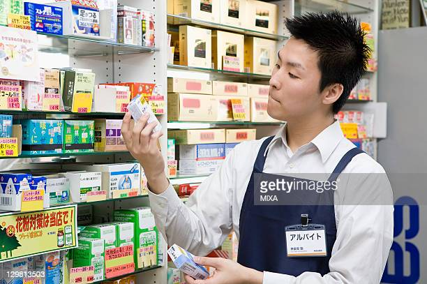Clerk of Drugstore Holding and Looking Merchandise