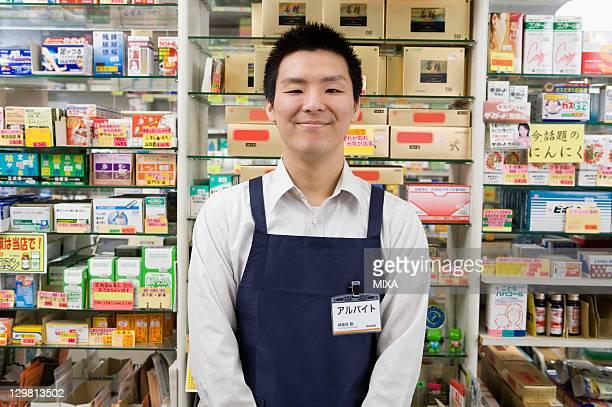 Clerk of Drugstore Standing in front of Shelves