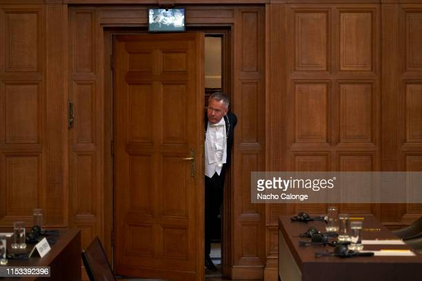Clerk of the court peers round a door into the courtroom at the International Court of Justice at the start of hearings on the preliminary objections...