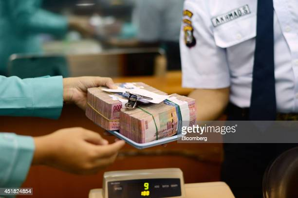 A clerk passes bundles of Indonesian 100000 rupiah banknotes to a security officer at a currency exchange office in Jakarta Indonesia on Monday July...