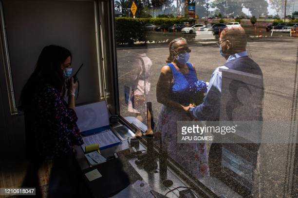 Clerk Recorder Erika Patronas officiates the wedding ceremony of Natasha and Michael Davis at the Honda Center parking lot on April 21 2020 in...