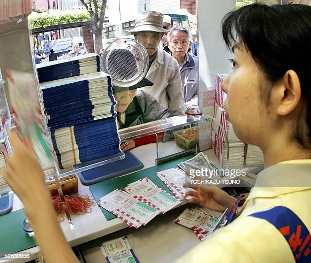 A clerk sells tickets for the 300 million yen Dream Jumbo Lottery at a Tokyo ticket booth 16 May 2005 Thousands of punters queued up for tickets in...