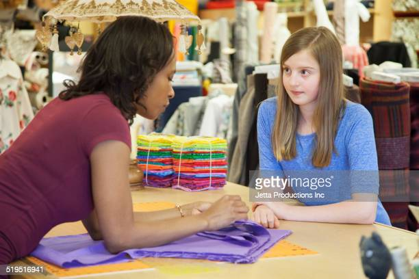 Clerk talking to customer in fabric store