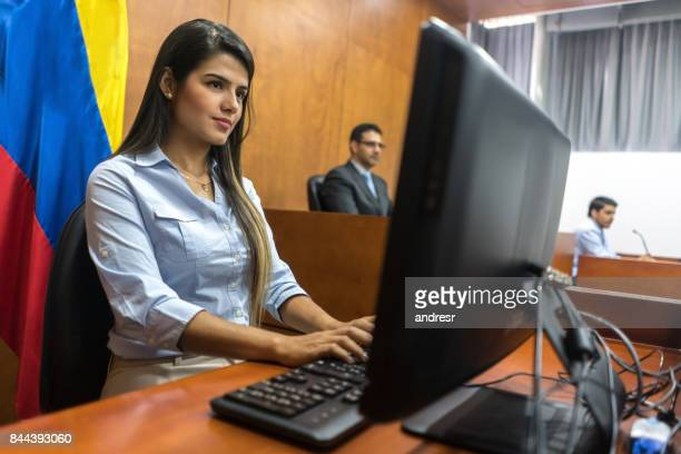 Clerk typing the session in trial at the courtroom