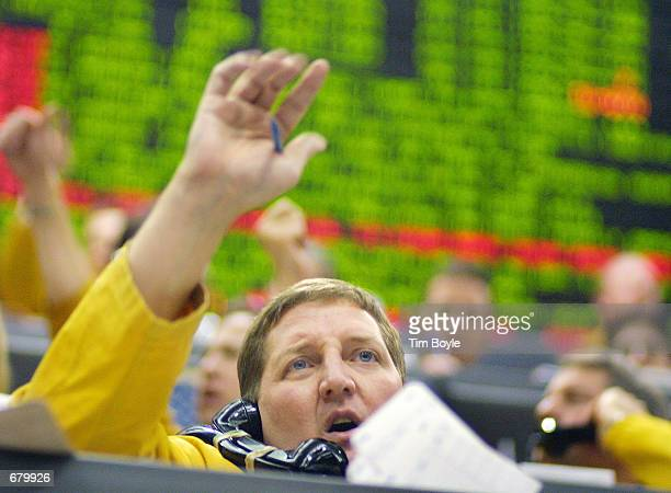Clerk works the phone as he hand-signals his trader in the Eurodollar Futures pit of the Chicago Mercantile Exchange November 6, 2001 after the FOMC...