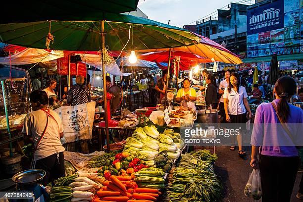 店員、新鮮な野菜を販売するナイトマーケット