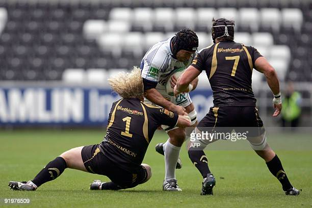 ClermontAuvergne's Jamie Cudmore is tackled by Ospreys' Duncan Jones and Marty Holah during the European Rugby Union Cup match at Liberty Stadium in...
