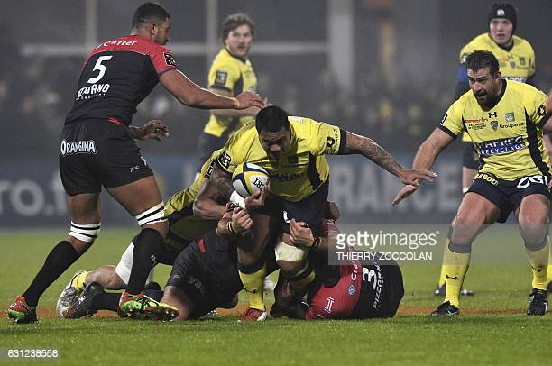 Clermont's Australian hooker John Ulugia is tacklednext to Clermont's French prop Raphael Chaume during the French union rugby match between ASM...