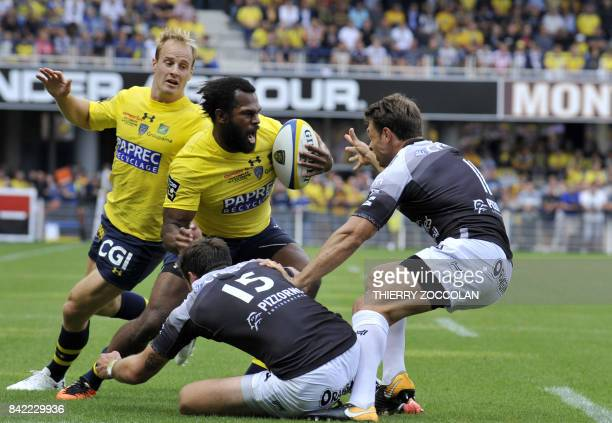 Clermont's Fijian winger Alivereti Raka escapes a tackle from RC Toulon's Italian fullback Edoardo Padovani and French winger Vincent Clerc during...