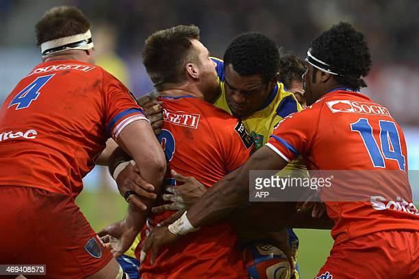 Clermont's Fijian winger Napolioni Vonowale Nalaga is tackled by Grenoble's Fijian winger Ratu Raitini and Grenoble's French hooker Anthony Hegarty...