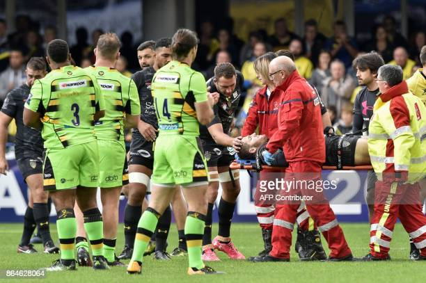 Clermont's French flyhalf Camille Lopez is being evacuated on a stretcher after suffering a broken shinbone during the European Rugby Champions Cup...