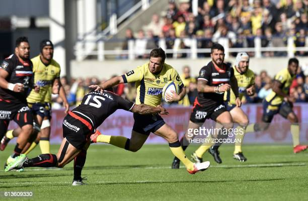 Clermont's French flyhalf Camille Lopez tries to escape the tackle from a player of Toulouse during the French Top 14 Rugby Union match ASM Clermont...