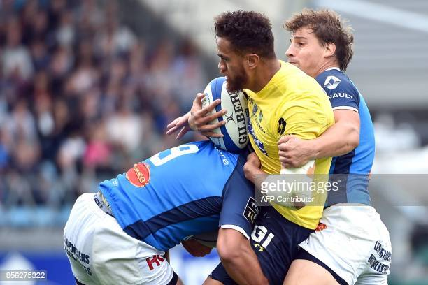 Clermont's New Zealander center Peter Betham his tackled by Castres's players during the French Top 14 rugby union match between Castres and Clermont...