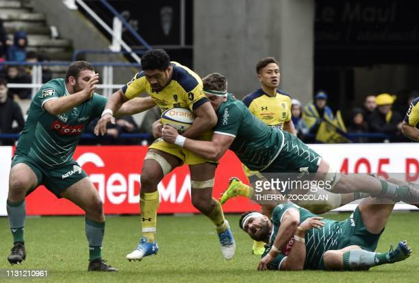 Clermont's Samoan flanker Fritz Lee is tackled by Pau players during the French Top 14 rugby match between Clermont and Pau at the Michelin stadium...