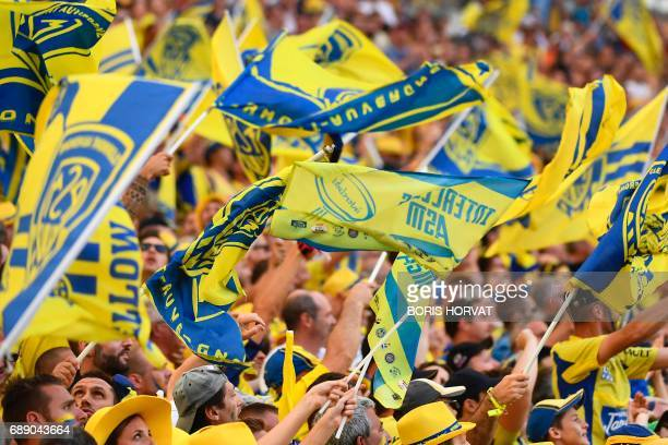 Clermont's supporters wave their team flag as they cheer during the French Top 14 rugby union semi-final match between Clermont and Racing 92 on May...