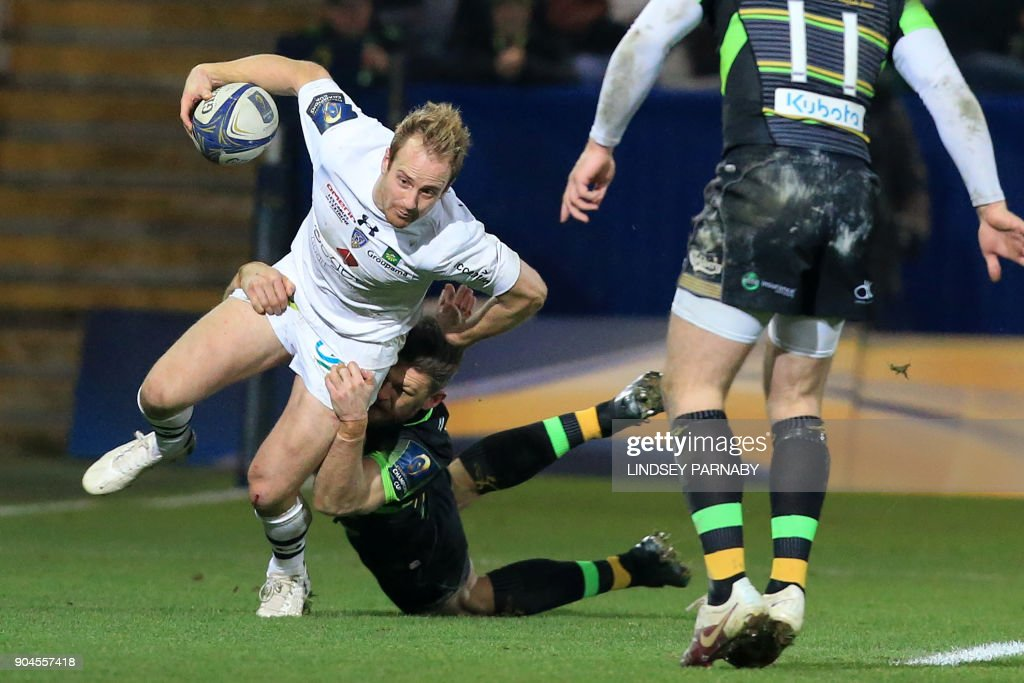 Clermont's wing Nick Abendanon (L) is tackled during the European Rugby Champions Cup rugby union match between Northampton Saints and Clermont Auvergne in Northampton on January 13, 2018. / AFP PHOTO / Lindsey PARNABY